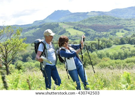Couple of senior hikers taking pictures with smartphone