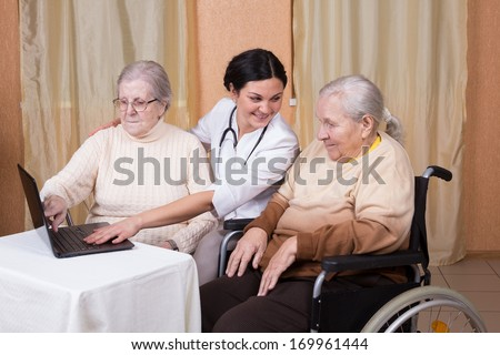 couple of senior Woman with carer Learning Computer Together - stock photo