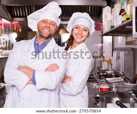 Couple of smiling cooks working together at kitchen in take-away restaurant  - stock photo