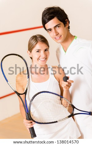 Couple of squash players at the court holding rackets - stock photo