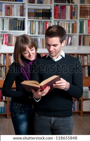Couple of students at the library reading a book - stock photo