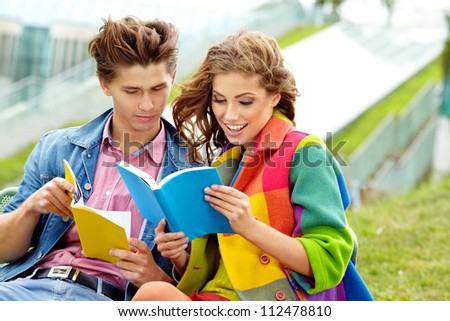 Couple of students sitting outdoors studying and smiling - stock photo