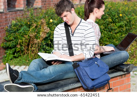 Couple of students using a laptop and reading a book sitting in the campus of their university - stock photo