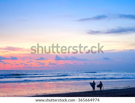 Couple of surfers walking on the beach on Bali island, Indonesia - stock photo