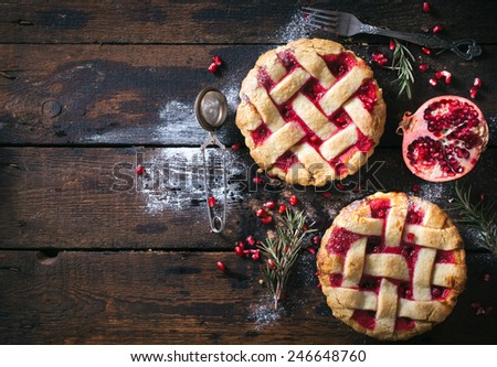 Couple of sweet tarts with pomegranate on wooden background with blank space  - stock photo