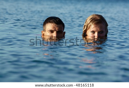 couple of swimmers coming up from the sea. lower parts of faces are in sea water - stock photo