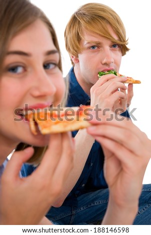 couple of teenagers eating pizza