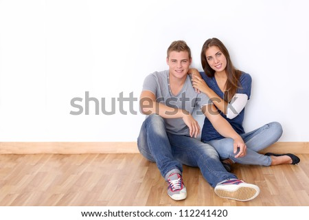 Couple of teenagers sitting against white wall - stock photo