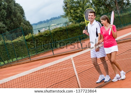 Couple of tennis players at the court and holding rackets - stock photo