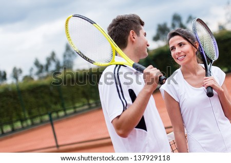 Couple of tennis players talking at the court after a match - stock photo