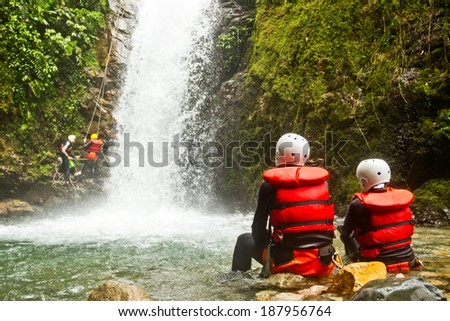 COUPLE OF TOURIST ADMIRING THE NATURAL BEAUTY OF A WATERFALL, CANYONING TRIP   - stock photo