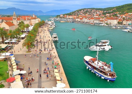 Couple of tourist boats maneuvering inside old Venetian town harbor in overcast day, Trogir, Croatia - stock photo
