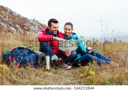 Couple of tourist reading map, sitting on the ground. - stock photo