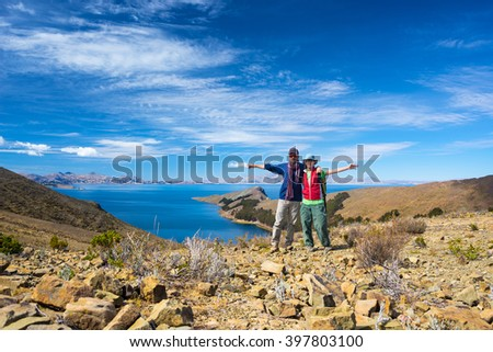 Couple of tourist with outstretched arms looking at camera on the Island of the Sun, Titicaca Lake, Bolivia. Concepts of wanderlust and people traveling around the world. Expansive view.