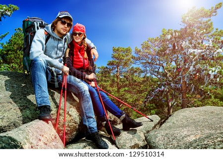 Couple of tourists are sitting at the top of a mountain with a feeling of freedom. - stock photo