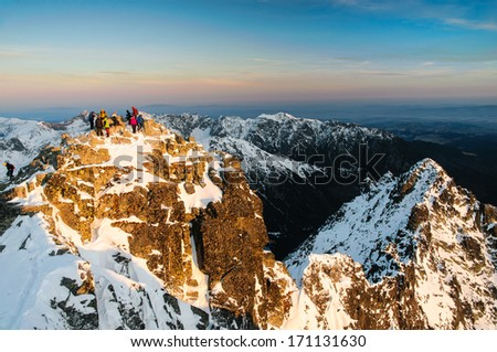 Couple of tourists climbed up the rugged summit of Rysy mountain in winter in High Tatras national park, Slovakia - stock photo