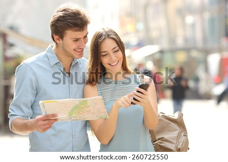 Couple of tourists consulting a city guide and smartphone gps in the street searching locations - stock photo