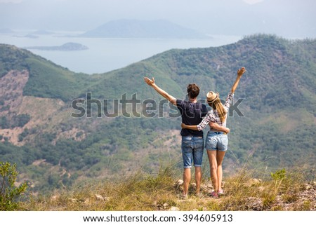 Couple of tourists hiking in mountains, enjoying beautiful view of lagoon and small islands far away