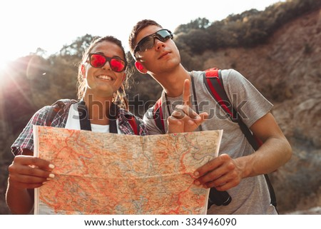 Couple of tourists hiking. Using map to get good direction. - stock photo