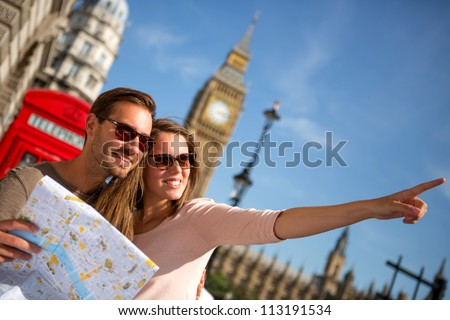 Couple of tourists in London holding a map - stock photo