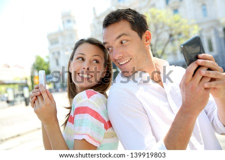 Couple of tourists in Madrid using smartphone