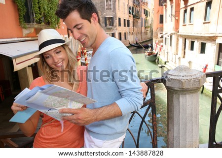 Couple of tourists in Venice looking at map by canal