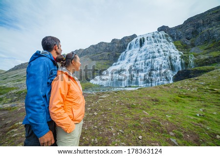 Couple of tourists near Dynjandi is the most famous and beautiful waterfall of the West Fjords in Iceland. - stock photo