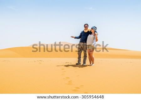 Couple of tourists posing on sand dunes in Merzouga, Morocco - stock photo