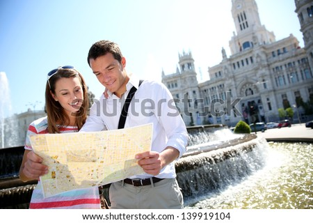Couple of tourists reading map in Plaza de Cibeles, Madrid - stock photo