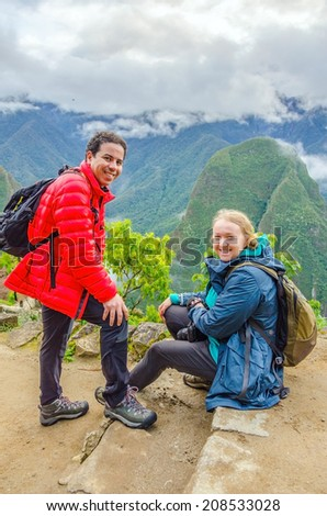 Couple of tourists resting in ruins of Machu Picchu, Peru