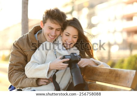 Couple of tourists reviewing photos in a dslr camera sitting in a bench of a park with an urban background - stock photo