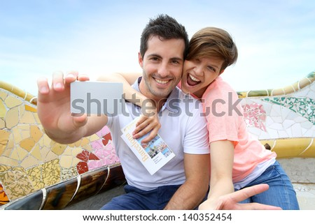 Couple of tourists showing Barcelona visitor's pass - stock photo