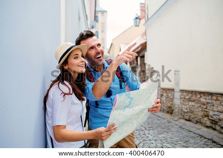 Couple of tourists sightseeing old european  town with map - stock photo