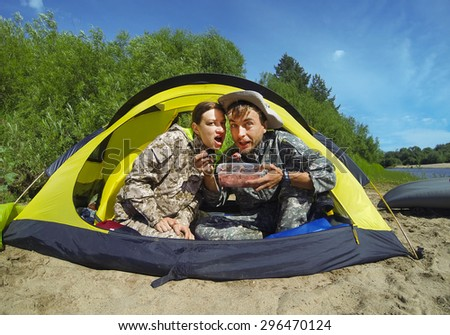 Couple of tourists sitting in a camping tent and eating - stock photo