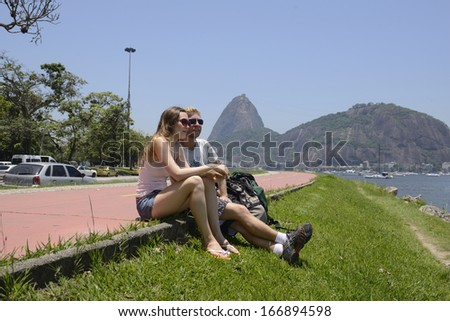 Couple of tourists sitting on the edge of Guanabara Bay with the Sugar Loaf in the background. - stock photo