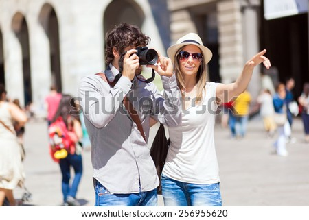 Couple of tourists taking picture in the city - stock photo