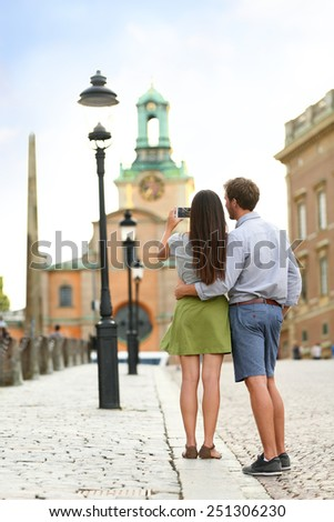 Couple of tourists taking travel pictures of Stockholm Cathedral (Storkyrkan) and Royal Palace, official residence of the Swedish monarch on Stadsholmen, in Gamla stan in the capital Stockholm. - stock photo