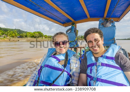 Couple of tourists traveling in touristic boat down the Beni river in Bolivian jungle (Rurrenabaque region) - stock photo