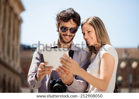 Couple of tourists using a digital tablet - stock photo