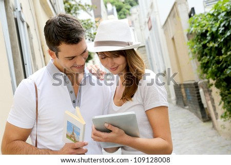 Couple of tourists using guide and tablet in town