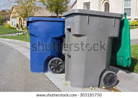 Couple of trash bins awaits pickup off a residential street. - stock photo