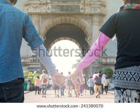 couple of traveler holding hands in front of the patuxai, Vientiane, public place in Laos - stock photo