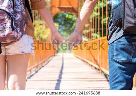 couple of traveler holding hands on the wooden bridge - stock photo