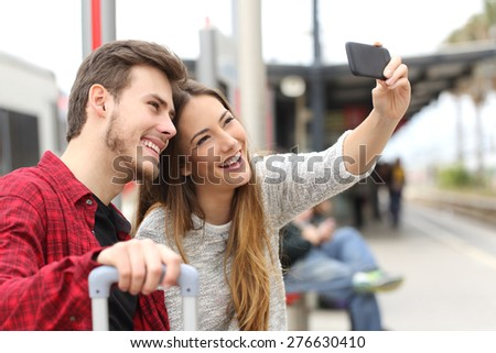 Couple of travelers photographing a selfie with a smartphone in a train station - stock photo