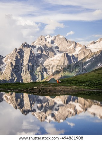 Couple of trekkers at tent and reflection of mountains in lake