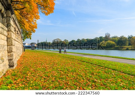 Couple of unidentified people riding bikes along a Vistula river in Krakow on sunny autumn day. Krakow is most visited city in Poland among foreign tourists. - stock photo
