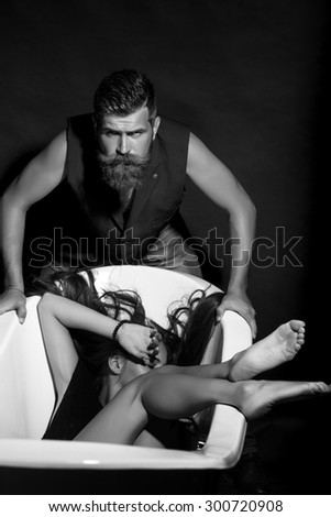 Couple of unshaven big strong man with beard and moustache in waistcoat standing near young hiding girl barefoot lying in bathtub black and white, vertical picture - stock photo