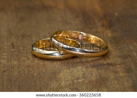 couple of wedding rings on wooden table - stock photo