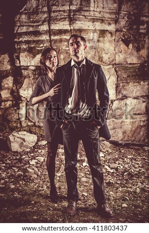 Couple of well dressed businessman and businesswoman on the dark rocks background.