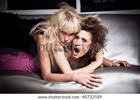 couple of wild girls on silver bed, indoor shot - stock photo